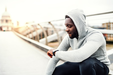 Young sporty black man runner with smart watch on the bridge in a city, resting. Stock Photo