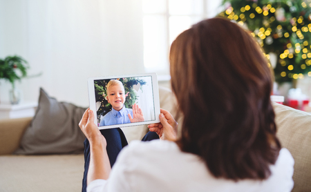 Senior woman with tablet talking with her grandson through online video phone call. Stockfoto