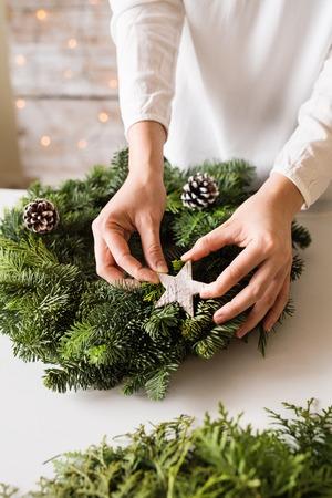 Eine nicht erkennbare Frau, die einen Weihnachtskranz schmückt.