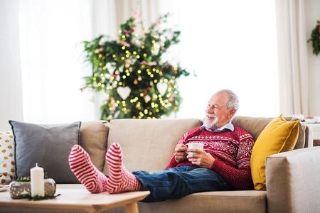 Un uomo anziano con una tazza di caffè seduto su un divano a casa nel periodo natalizio.