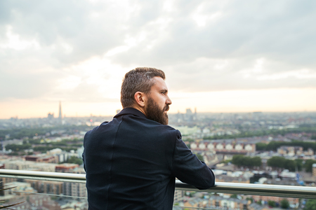 A rear view of businessman standing against London view panorama.
