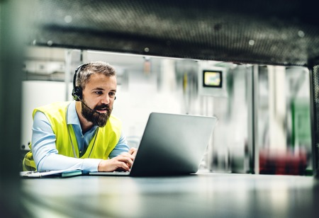 An industrial man engineer with headset and laptop in a factory, working. Banque d'images