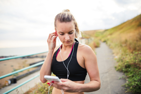 Young sporty woman runner with earphones and smartphone standing by the seaside.