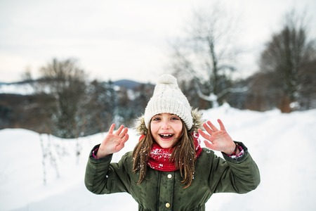 Portrait of a small girl in winter nature, wearing coat, hat and scarf. Stock Photo