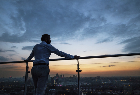 A rear view of businessman standing against London view panorama at dusk.