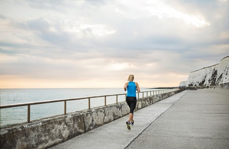 Rear view of young sporty woman runner running on the beach outside. Stock Photo