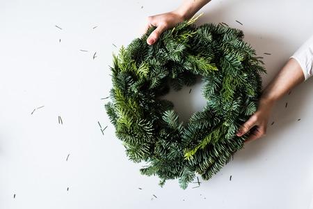 Weibliche Hände, die grünen Weihnachtskranz halten. Draufsicht. Speicherplatz kopieren. Standard-Bild