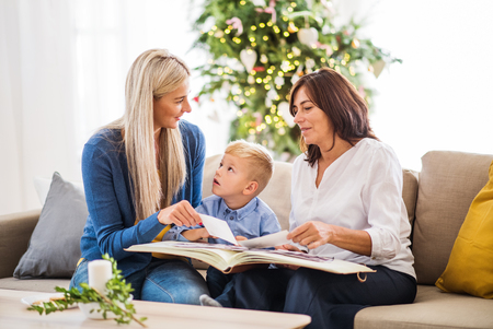 A small boy with mother and grandmother looking at photos at home at Christmas time. Stockfoto
