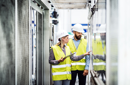 A portrait of an industrial man and woman engineer with tablet in a factory, working. Stockfoto