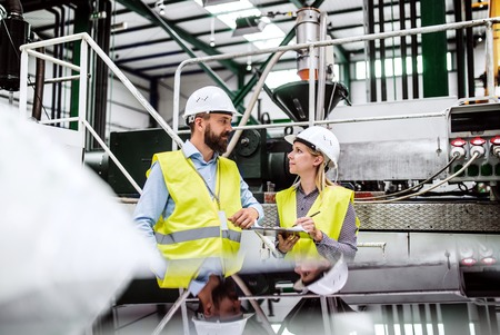 A portrait of an industrial man and woman engineer with clipboard in a factory, working.