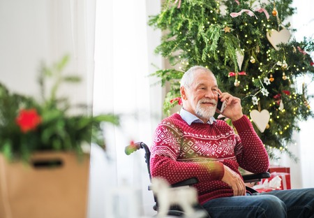 A senior man in wheelchair with mobile phone at home at Christmas time, making a phone call. Фото со стока