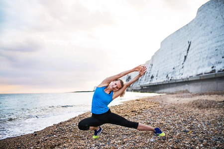 Young sporty woman runner in blue sportswear stretching on the beach outside. Stock Photo