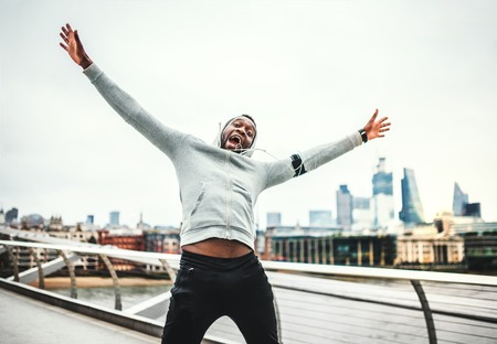 Black man runner on the bridge in a city, resting and having fun.