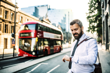 Hipster businessman standing on the street in London, checking the time.