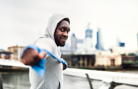 Young black sportsman exercising with elastic rubber bands in London. 免版税图像