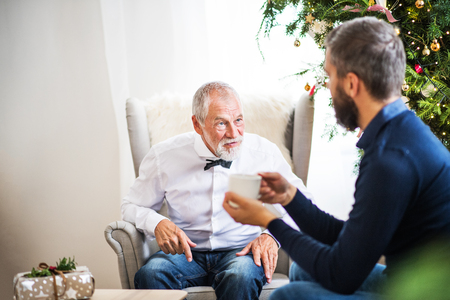 A senior father and adult son sitting on a sofa at Christmas time, talking. Stok Fotoğraf