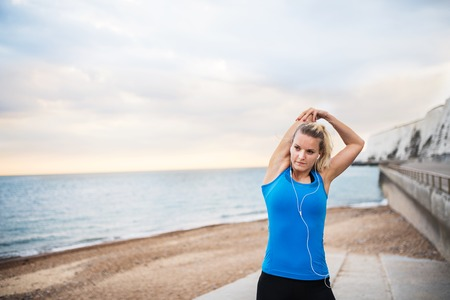Young sporty woman runner with earphones standing on the beach outside, stretching. Stock Photo