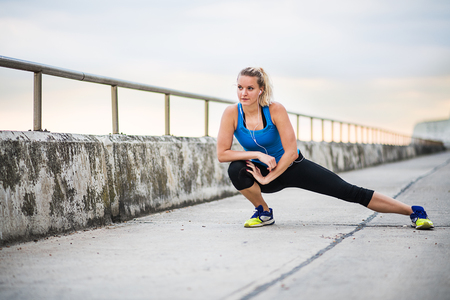 Young sporty woman runner with earphones stretching by the sea outside.