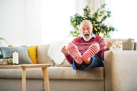 A cheerful senior man with red and white socks at home at Christmas time, having fun.