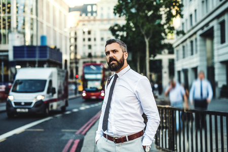 Hipster businessman standing on the street in London next to a busy road.
