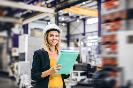 A portrait of an industrial woman engineer in a factory, checking something.