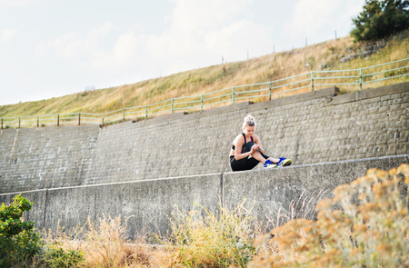 Young sporty woman runner sitting on a concrete wall outside, resting.