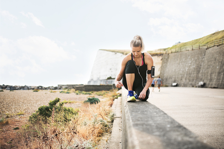 Young sporty woman runner with earphones tying shoelaces by the beach.