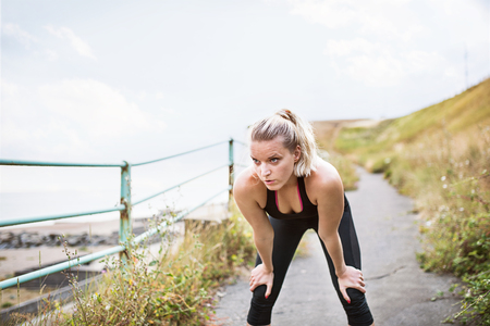 Young sporty woman runner in black activewear standing outside by the seaside, resting. Stock Photo