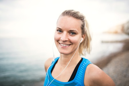 Young sporty woman runner with earphones standing on the beach outside.