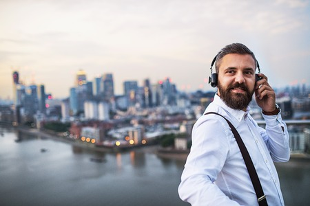 A businessman with headphones standing against London view panorama. Copy space. Stock Photo