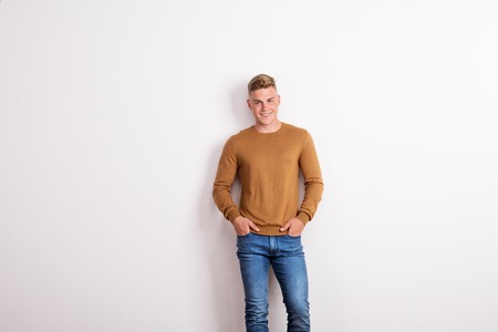 Portrait of a happy young man standing in a studio, hands in pockets. Stockfoto