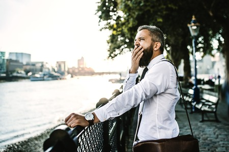 A tired businessman standing by the river in London at sunset. Reklamní fotografie