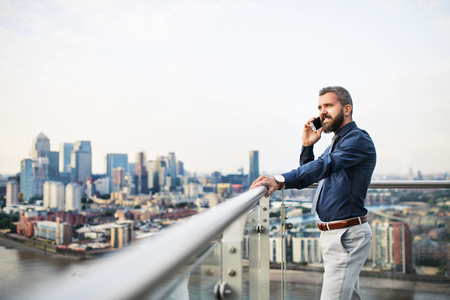 A portrait of businessman with smartphone standing against London view panorama. Standard-Bild - 110971788