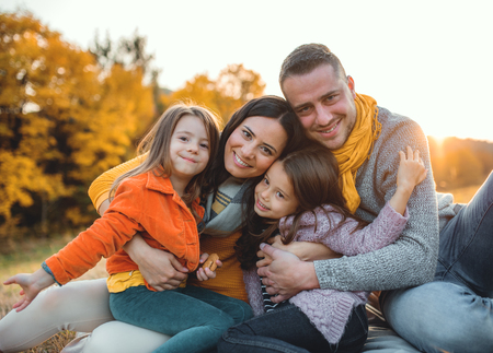 A portrait of young family with two small children in autumn nature at sunset.