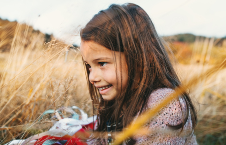 A small girl playing with a rainbow hand kite in autumn nature. Stock Photo