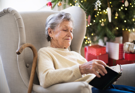 A lonely senior woman reading Bible at home at Christmas time.