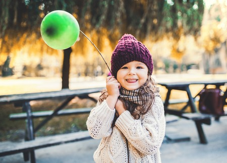 A portrait of a small toddler girl holding balloon in park in autumn nature.