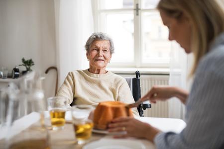 Eine ältere Frau im Rollstuhl mit einem Gesundheitsbesucher, der zu Hause am Tisch sitzt.