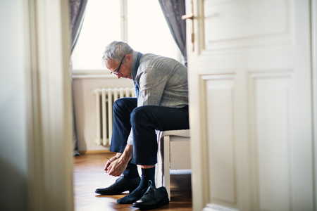 Mature businessman on a business trip sitting in a hotel room, tying shoelaces.