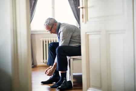 Reifer Geschäftsmann auf einer Geschäftsreise in einem Hotelzimmer sitzend, Schnürsenkel binden.
