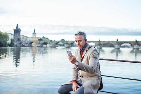 Mature businessman with smartphone sitting by river Vltava in Prague city.