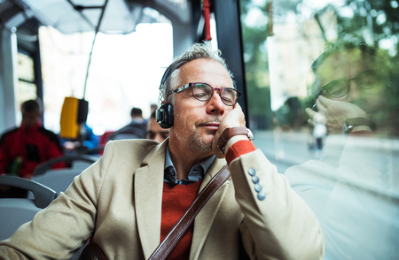 Mature tired businessman with heaphones travelling by bus in city. Stock Photo