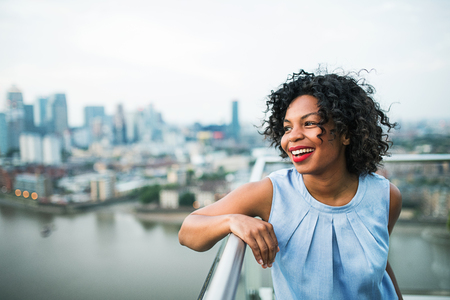 A portrait of a woman standing on a terrace in London. Copy space.