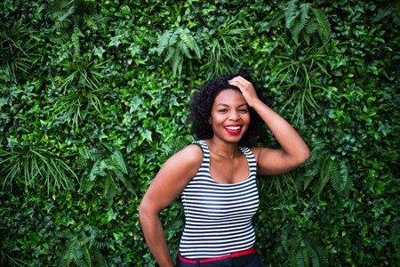 A portrait of a black woman standing against green background of bush leaves. Banco de Imagens