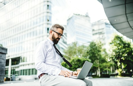 Hipster businessman with laptop sitting outdoors in the city. Фото со стока - 111260582