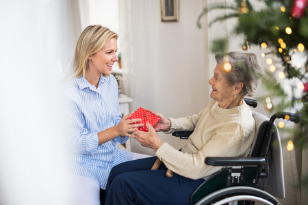 Health visitor and senior woman in wheelchair with a present at home at Christmas. 스톡 콘텐츠