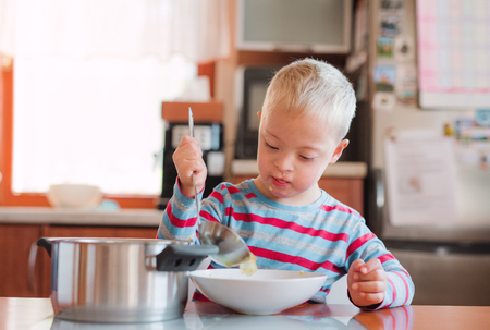 A handicapped down syndrome child pouring soup into a plate indoors. Archivio Fotografico - 111260600