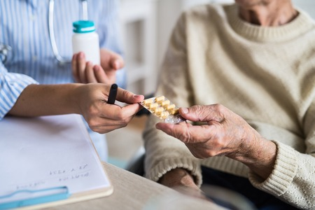 An unrecognizable health visitor explaining a senior woman in wheelchair how to take pills. Stockfoto