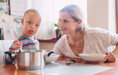 Un bambino disabile con sindrome di Down con sua madre in casa a mangiare il pranzo.