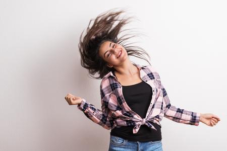 Young beautiful happy woman in studio, wind in the hair.